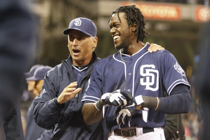 Padres' manager Bud Black congratulates Cameron Maybin after he made the game winning hit to beat the National 4-3 in the 11th inning.