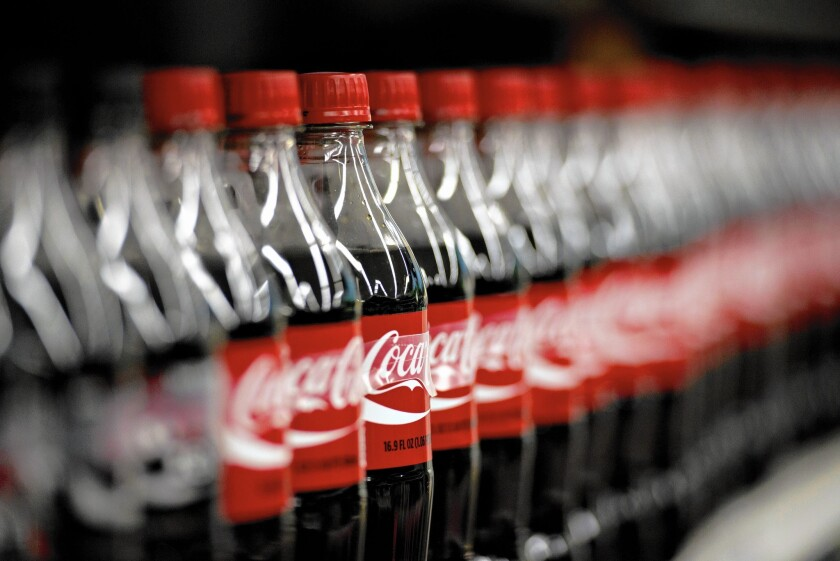 Bottles of Coca-Cola sit on a supermarket shelf in Princeton, Ill. A recent study found that sodas, sports drinks, energy drinks, fruit drinks and other sugary drinks accounted for nearly half of added sugars in U.S. diets.