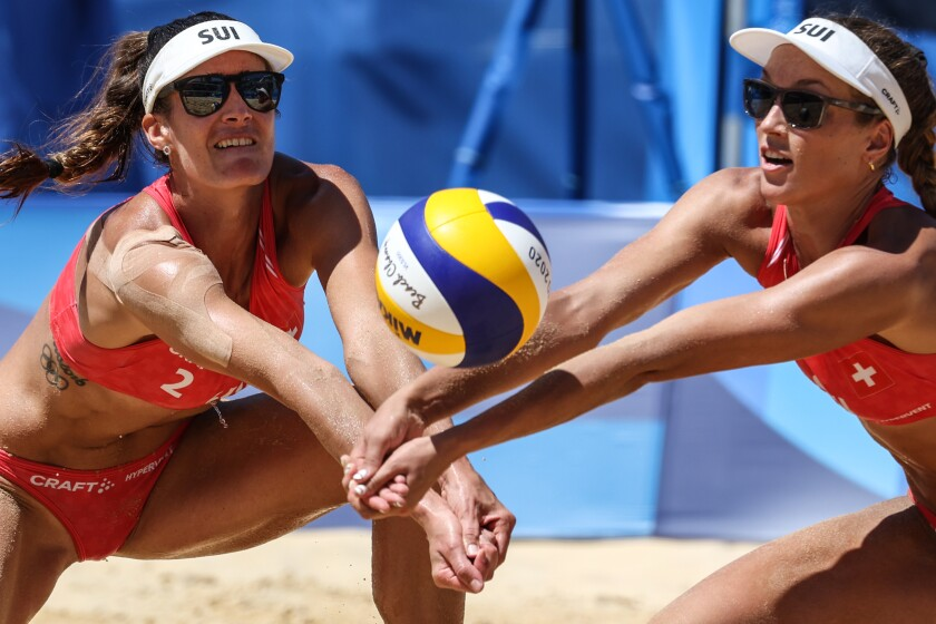 Nina Betschart has tape on her shoulder as she and Swiss teammate Tanja Huberli play volleyball at the Tokyo Olympics.