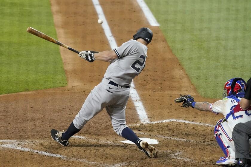 New York Yankees second baseman DJ LeMahieu follows through on a two-run double as Texas Rangers catcher Jonah Heim looks on in the fourth inning of a baseball game in Arlington, Texas, Tuesday, May 18, 2021. (AP Photo/Tony Gutierrez)