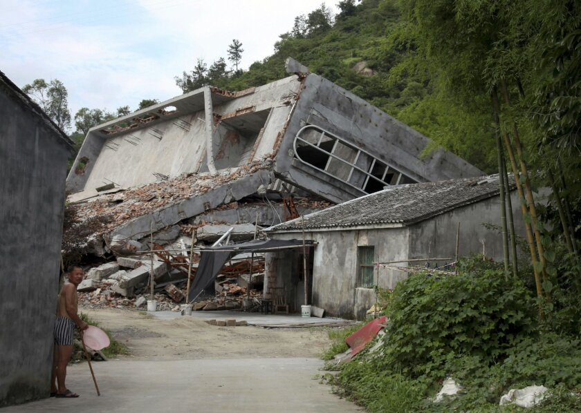 File- This July 16, 2014, file photo a man stands near the razed remains of a Catholic church in a village in Pingyang county of Wenzhou in eastern China's Zhejiang province. Since taking the presidency in 2013 and becoming the most powerful Chinese leader in three decades, President Xi Jinping has cracked down on encroachment of what he views as Western-style freedoms in China's increasingly prosperous and connected society. His administration has also tightened controls on religious minorities, including a government campaign to remove crosses and demolish Christian churches in an eastern province — a move that has drawn condemnation in the U.S. Congress. (AP Photo/Didi Tang, File)