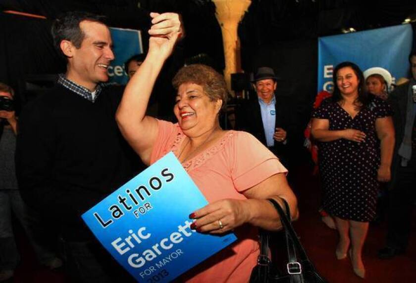 Eric Garcetti, who is running for Los Angeles mayor, dances with supporter Ana Castro at a campaign meeting in East Los Angeles. Garcetti is stressing his multicultural heritage during his campaign.