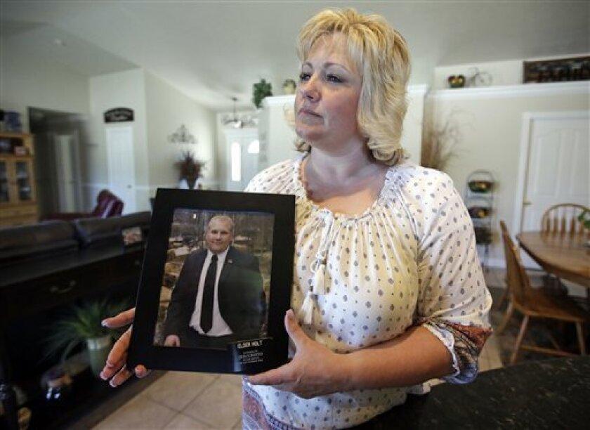 En esta imagen del 13 de julio de 2016, Laurie Holt sostiene una fotografía de su hijo, Josh Holt, en su casa de Riverton, Utah. Josh Holt, un estadounidense de 24 años que está encarcelado en Venezuela por cargos de posesión de armas, describió el acoso policiaco y que fue obligado a dormir en una celda caliente apenas lo suficientemente grande para albergar una cama, en lo que es su primera comunicación desde la cárcel.