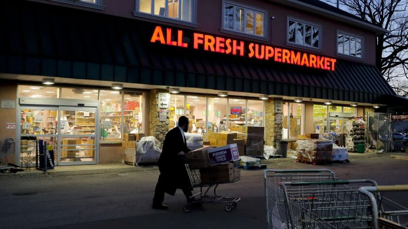 An orthodox Jewish man walks through the parking lot of a supermarket, Tuesday, March 26, 2019, in S