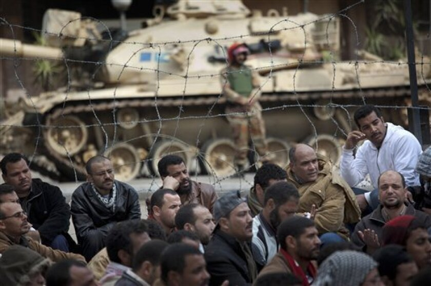An soldier stands guard next to a tank, as anti-government protesters sit on the ground during a protest in front of the state television building on the Corniche in downtown Cairo, Egypt, Friday, Feb. 11, 2011. Mubarak refused to step down or leave the country and instead handed his powers to his