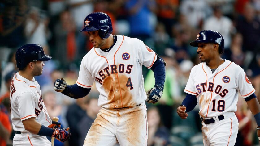 George Springer, center, is congratulated by Houston Astros teammates Jose Altuve, left, and Tony Ke
