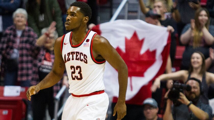 A fan waves a Canadian flag for SDSU guard Montaque Gill-Caesar after making a basket.