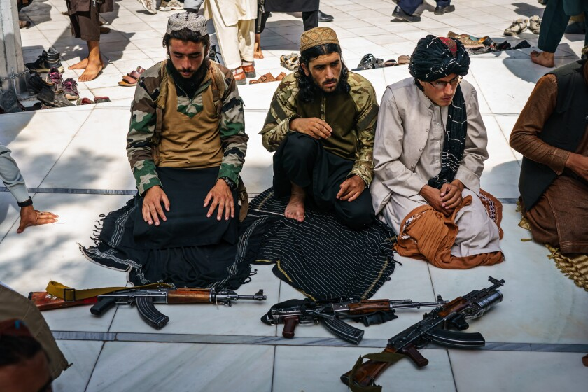 Taliban fighters kneeling alongside their weapons for Friday prayers