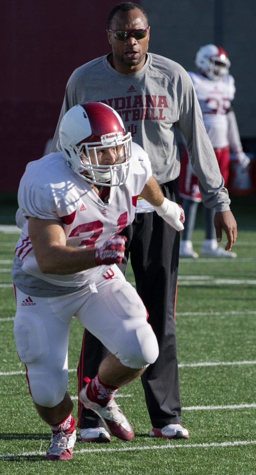 James Halford, foreground, runs as co-defensive coordinator William Inge watches Halford during an NCAA college football practice Wednesday, Nov. 4, 2015, in Bloomington, Ind. Halford cherishes the football apprenticeship Indiana gave him as a scout team linebacker and fullback, and he will always
