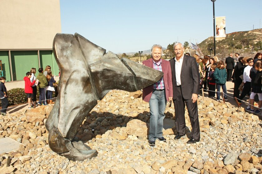Artist Jose Sacal and San Diego Jewish Academy Executive Director Larry Acheatel pose with the bronze statue 'First Step,' which stands 7 feet high and 7 feet wide, and weighs more than 700 pounds. Courtesy