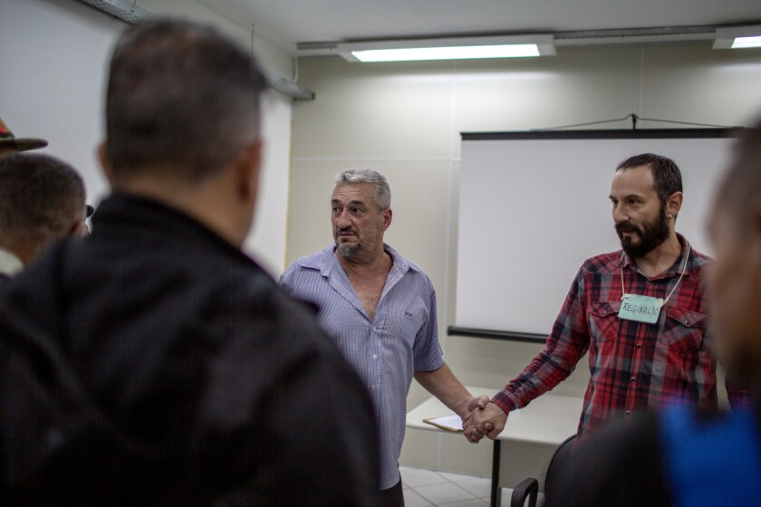 Ricardo Serafine, left, holds the hand of group facilitator Reginaldo Bombini as they and other participants of a therapy group for men serving alternative sentences for domestic violence convictions wrap up their session with final words of support.