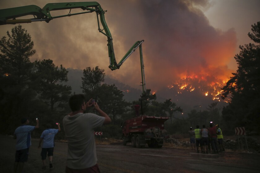 People watch an advancing fire that rages Cokertme village, near Bodrum, Turkey, Monday, Aug. 2, 2021. For the sixth straight day, Turkish firefighters battled Monday to control the blazes that are tearing through forests near Turkey's beach destinations. Fed by strong winds and scorching temperatures, the fires that began Wednesday have left eight people dead. Residents and tourists have fled vacation resorts in flotillas of small boats or convoys of cars and trucks. (AP Photo/Emre Tazegul)