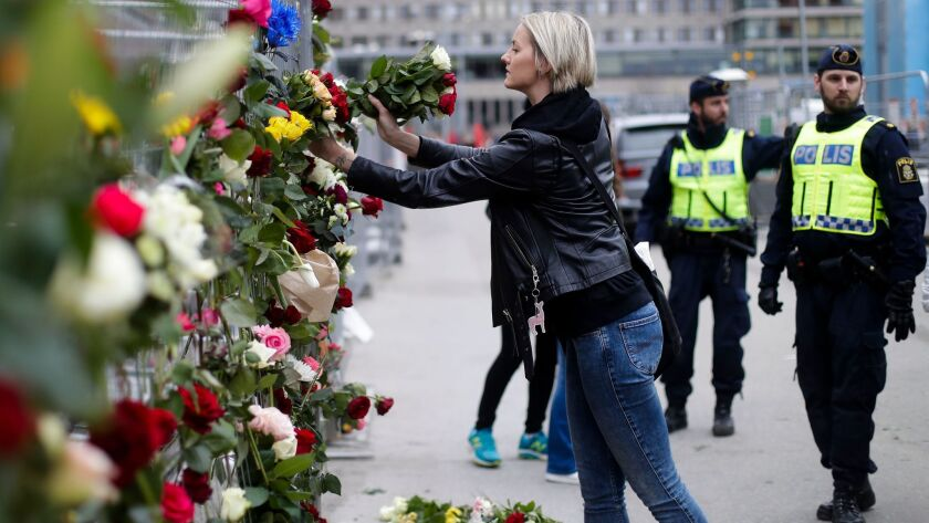 A woman places flowers on a fence following a suspected terror attack in central Stockholm, Sweden,