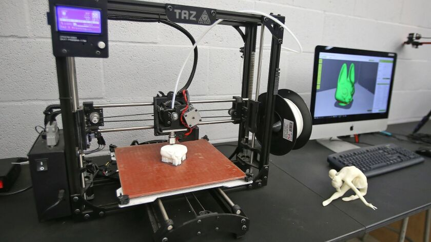 A TAZ 3D printer creates a plastic 3D model, left, and prints from the image on a computer, at right