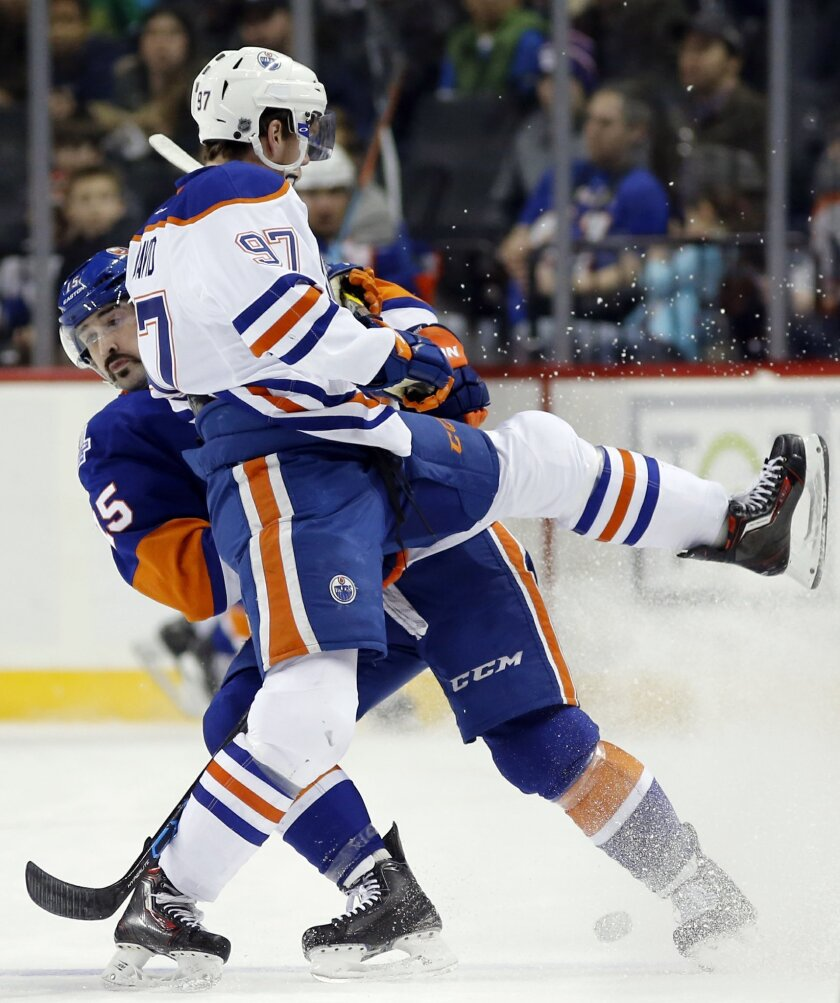 Edmonton Oilers center Connor McDavid (97) collides with New York Islanders right wing Cal Clutterbuck (15) in the first period of an NHL hockey game in New York, Sunday, Feb. 7, 2016. (AP Photo/Kathy Willens)