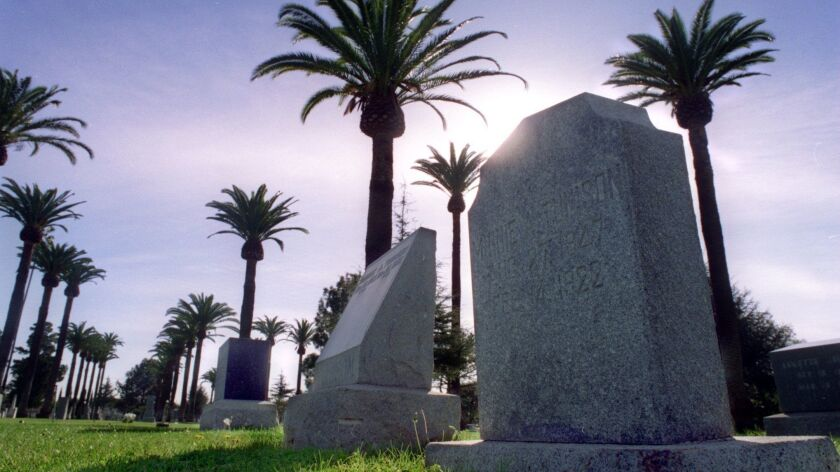 Palm trees provide a backdrop for a row of headstones at Santa Ana Cemetery.