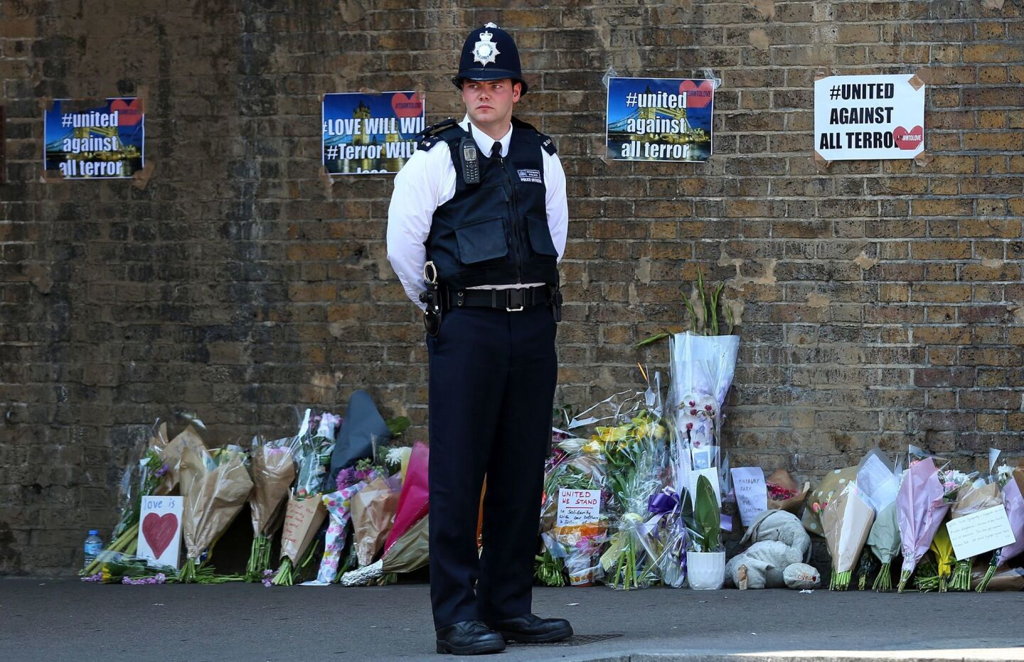 A police officer stands on duty near tributes and flowers at a police cordon in the Finsbury Park area of north London following a vehicle attack on pedestrians. One person died and 10 people were injured when a van drove into a crowd of Muslim worshippers near a mosque in London in the early hours of Monday.