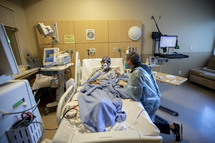 Chaplain Kevin Deegan kneels beside Domingo Benitez in COVID unit at Providence Holy Cross Medical Center in Mission Hills.