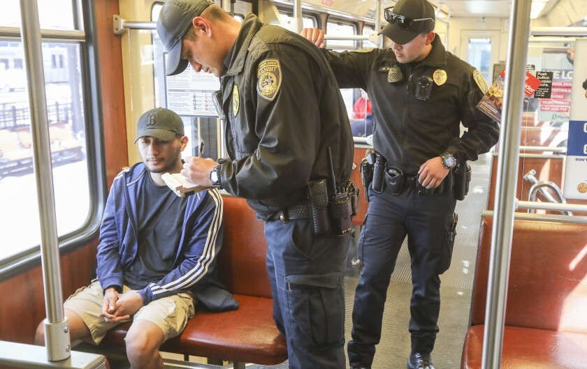 Transit officer Marc Vargas (middle), who does code compliance transit enforcement for the San Diego Metropolitan Transit System, writes a ticket to Bryan Marquez (left) on the Green Line on January 9, 2020. In the background (right) is transit officer Ramon Garcia who provides security for Vargas.