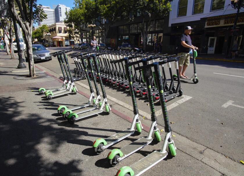 Marked corral space on 4th Avenue in downtown San Diego is packed full with scooters with nine other scooters parked just outside the corral and on sidewalk.