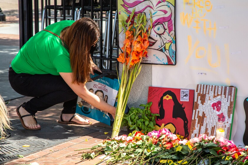 Comics fans like Mariel Delmar have been leaving memorabilia at a memorial across from the San Diego Convention Center.