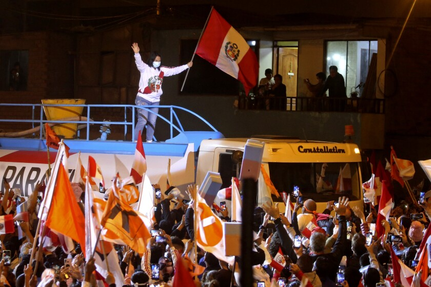 Keiko Fujimori waves from above a large vehicle to supporters below