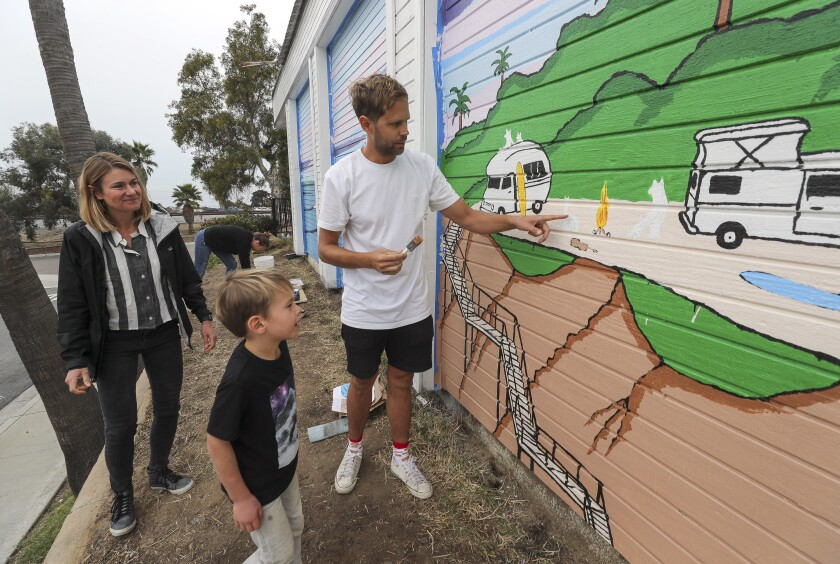 "Swedish artist Jonas Claesson shows Wilson MacDowell, 6, son of Tate MacDowell, 39, a Cardiff resident who died of cancer in October, a camp fire scene that is part of a mural-painting inspired from a watercolor done by his father, titled ""More Green Flashes."" Wilson's mother Lora Bodmer MacDowell stands nearby the mural on the back wall of the Cardiff 7-Eleven convenience store on Tuesday, December 3, 2019 in Encinitas, California."
