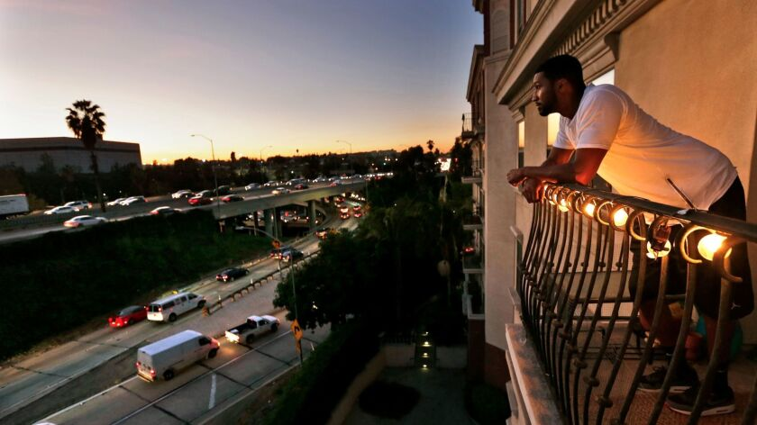 A renter at The Orsini apartments looks out from his 7th floor balcony at rush hour traffic on the 101 & 110 freeway interchange in Los Angeles on Nov 18, 2015.
