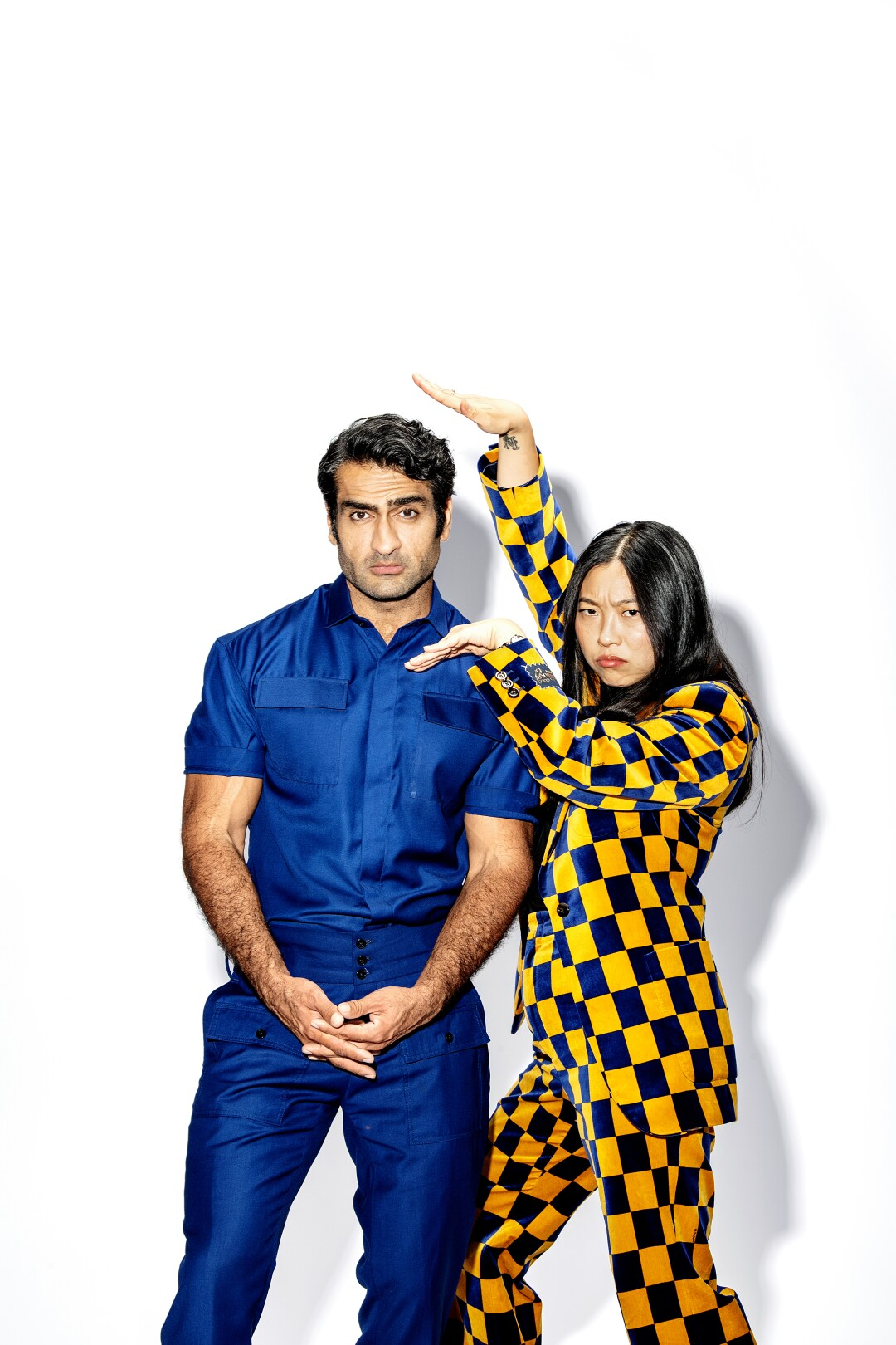 A man with dark hair in a blue outfit, left, stands next to a woman in a yellow-and-black checkered suit striking a pose