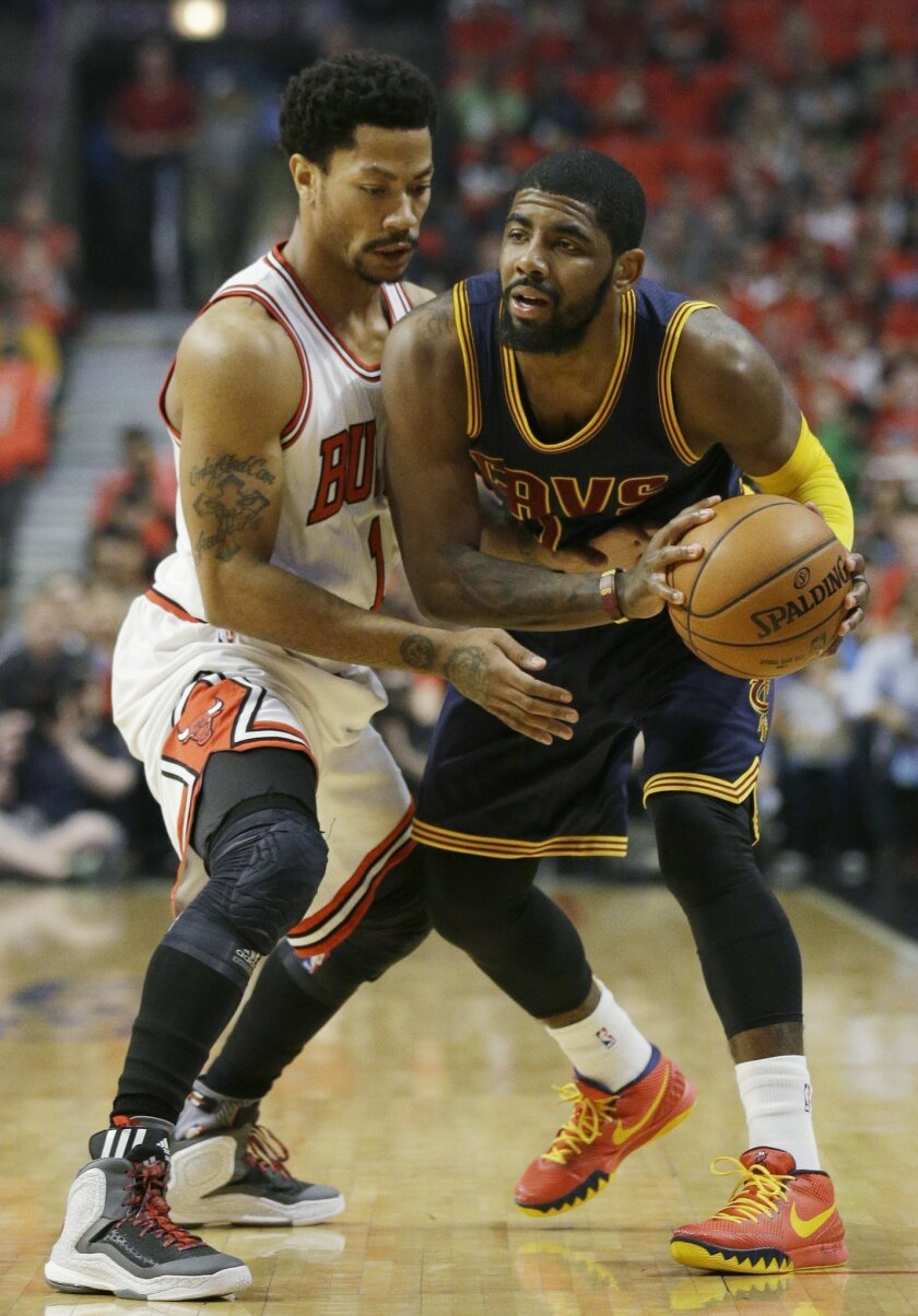 Cleveland Cavaliers guard Kyrie Irving, right, looks to a pass as Chicago Bulls guard Derrick Rose applies pressure during the first half of Game 3 in a second-round NBA basketball playoff series in Chicago on Friday, May 8, 2015. (AP Photo/Nam Y. Huh)