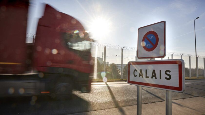 3070716_la-fg-brexit-calais CALAIS, FRANCE: Trucks pass the Calais sign on the outskirts of the po