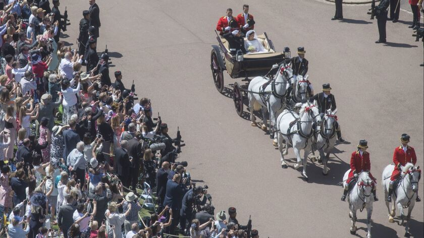 Meghan Markle and Prince Harry ride through Windsor Castle in an Ascot Landau after their wedding at