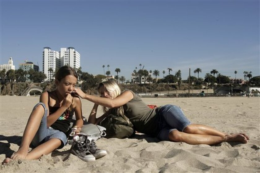 Flore Grandhomme, 37, with her daughter Naomi Deffarges, 11, relax at Santa Monica beach during an eight hour stopover on a flight home to France Monday, Jan. 12, 2009, in Santa Monica.