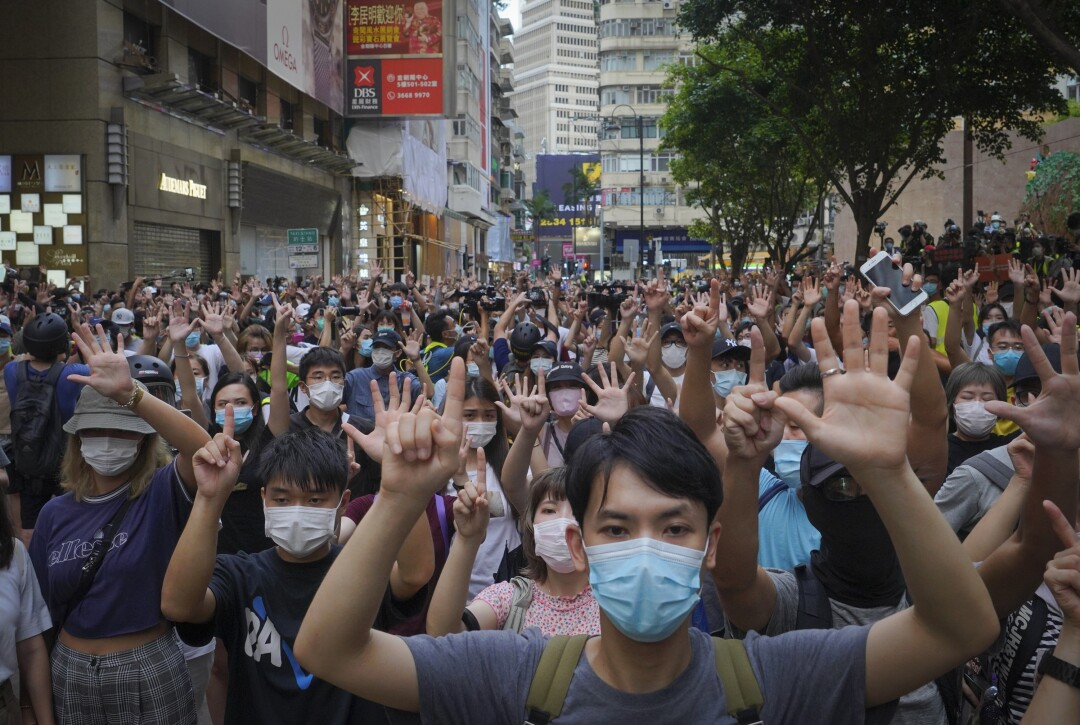 Protesters against Hong Kong's new national security law gesture with five fingers.