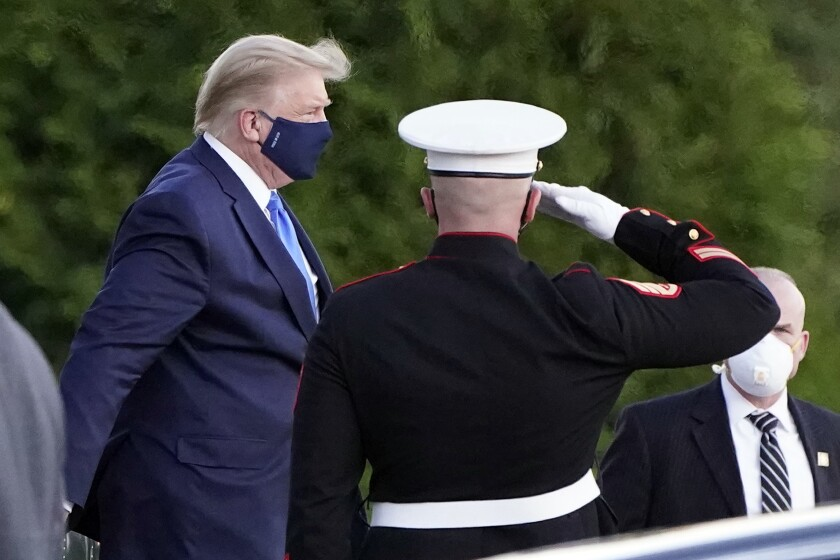 President Trump in a mask walks past a saluting Marine