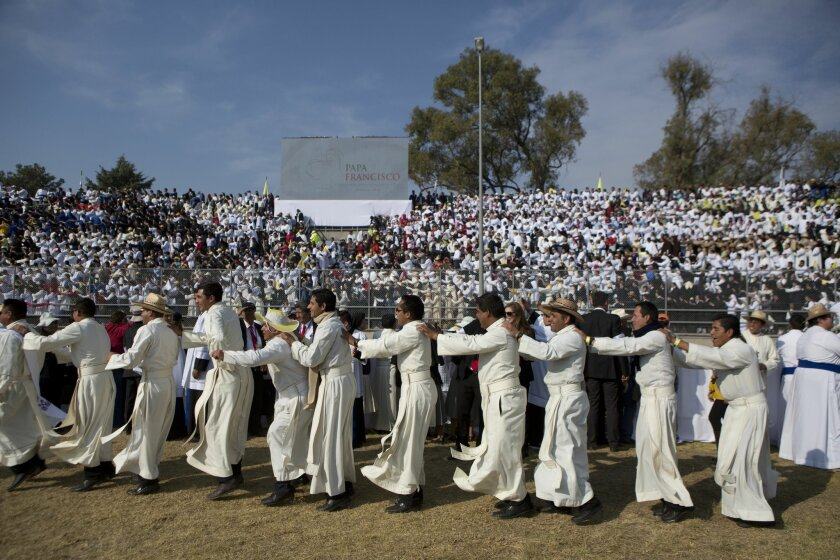 Religious men jump backwards as the crowd joins in a well known dance played over the loudspeakers, as they await the arrival of Pope Francis at Venustiano Carranza stadium in Morelia, Mexico, Tuesday, Feb. 16, 2016. On his one-day trip to the capital of troubled Michoacan state, the Pope will also