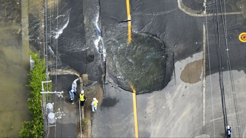 Water from damaged mains floods out from a crack in the road following an earthquake in Osaka, Japan, on June 18.