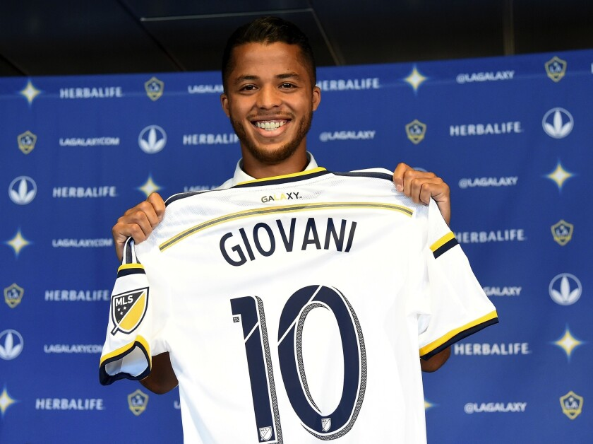 Giovani Dos Santos #10 of the Los Angeles Galaxy holds up his new jersey at a press conference at StubHub Center on August 4, 2015 in Carson, California.
