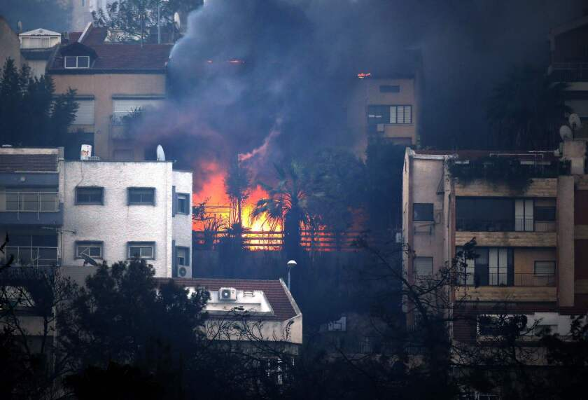Smoke billows from a house in the northern Israeli port city of Haifa.