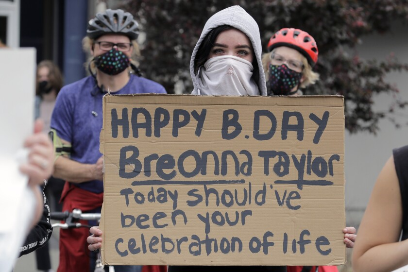 """A protester holds a cardboard sign reading: """"Happy B. Day Breonna Taylor — Today should've been your celebration of life."""""""