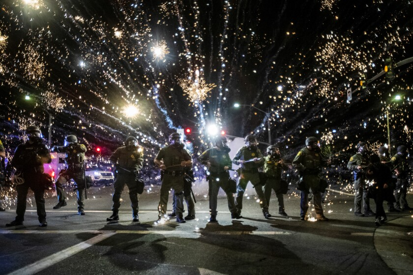 SANTA ANA, CA - MAY 30, 2020: Orange County Sheriff deputies maintain a police block as a firecracker thrown by a protester explodes behind them during a protest against the Minneapolis police killing of George Floyd during the coronavirus pandemic on May 30, 2020 in Santa Ana, California.
