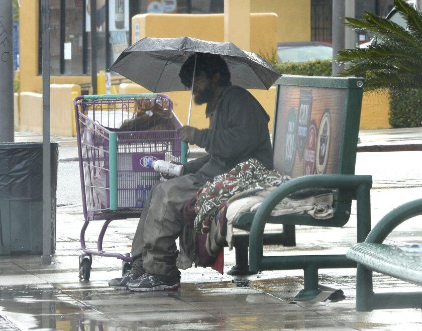 Homeless man outside in El Niño storm