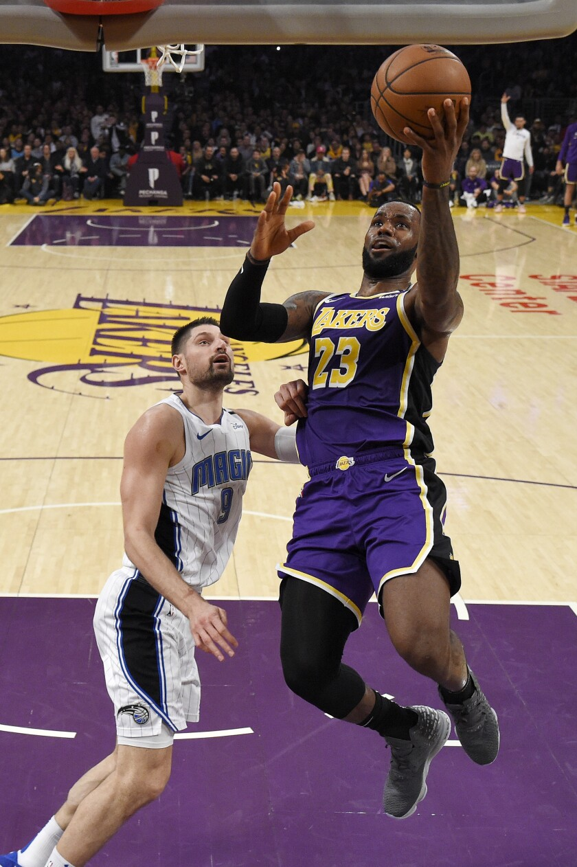 FILE - In this Jan. 15, 2020, file photo, Los Angeles Lakers forward LeBron James, right, shoots as Orlando Magic center Nikola Vucevic defends during the second half of an NBA basketball game, in Los Angeles. The Milwaukee Bucks and Los Angeles Lakers already have just about guaranteed themselves the top two playoff seeds and face a delicate balancing act when the NBA returns to action. They must try to shake off the rust after a 4 ½-month hiatus while also staying as healthy as possible for the postseason. (AP Photo/Mark J. Terrill, File)