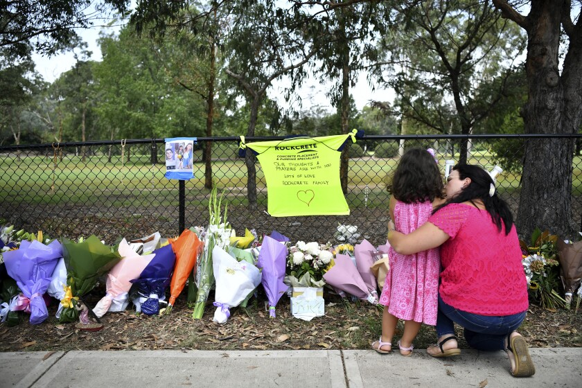 A woman pauses with a young girl near flowers placed at the scene where seven children were hit on a footpath by a four-wheel drive in the Sydney suburb of Oatlands, Sunday, Feb. 2, 2020. A 29-year-old man has been charged with 20 offences including manslaughter and high-range drink driving after four children were killed in Sydney on Saturday night. (Joel Carrett/AAP Image via AP)