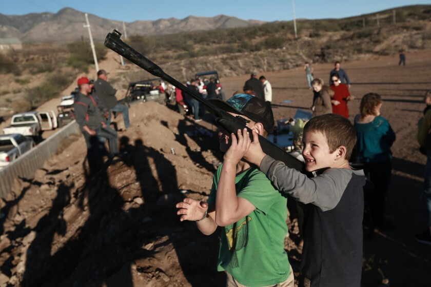 Boys point an unloaded gun at the sky as they play in La Mora, Mexico, one day before the expected arrival of Mexican President Andrés Manuel López Obrador, Saturday, Jan. 11, 2020. Three women and six of their children from La Mora, all U.S. citizens from the extended LeBaron family, were slaughtered and one of their cars burned by gunmen in this area on Nov. 4, 2019. (AP Photo/Christian Chavez)