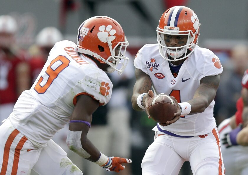 Clemson quarterback Deshaun Watson hands off to Wayne Gallman (9) during the first half of an NCAA college football game against North Carolina State in Raleigh, N.C., Saturday, Oct. 31, 2015. (AP Photo/Gerry Broome)
