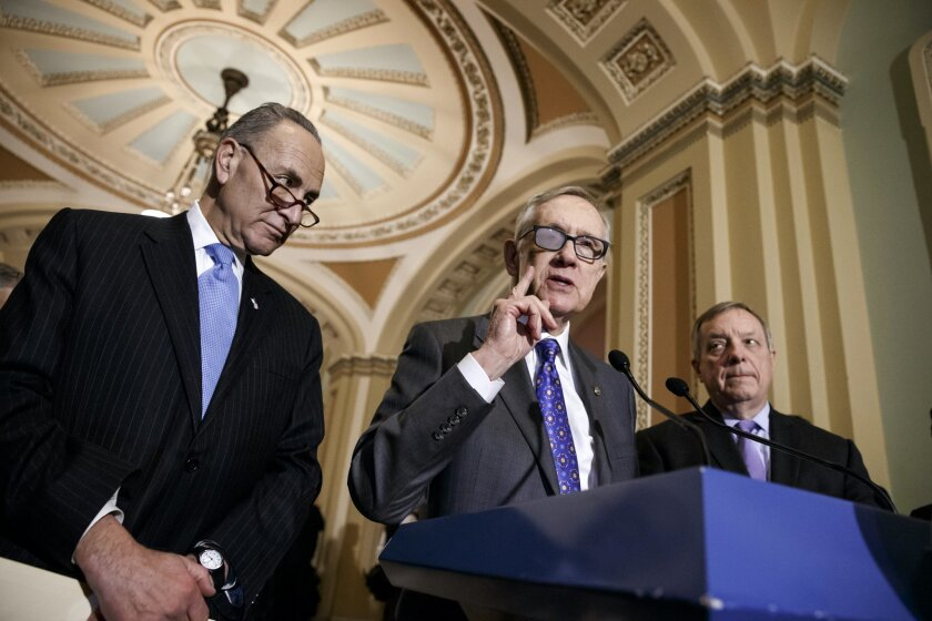 FILE - In this March 3, 2015 file photo, Senate Minority Leader Harry Reid of Nev., center, flanked by Sen. Charles Schumer, D-N.Y., left, and Senate Minority Whip Richard Durbin of Ill., speaks during a news conference on Capitol Hill in Washington. In the wake of the announced retirement of Reid, a very public feud has opened between the No. 2 and No. 3 Senate Democrats and former long-time housemates, Schumer and Durbin. (AP Photo/J. Scott Applewhite, File)