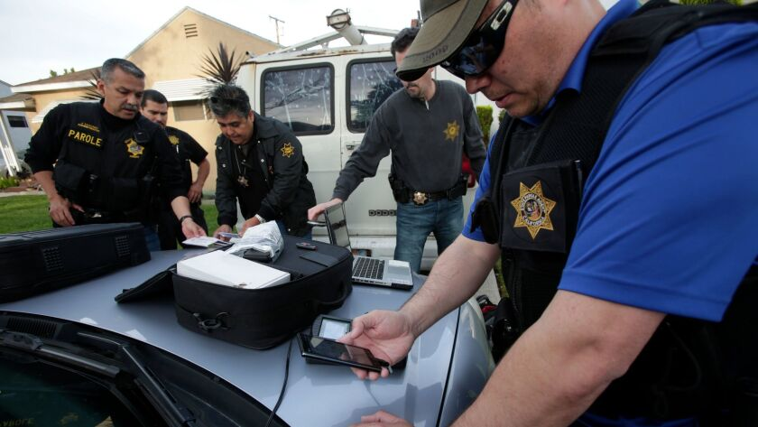 Parole agents watch their colleague Thomas Adams use an electronic device to check a sex offender's mobile phone, thumb drives and laptop for prohibited material on April 09, 2014.