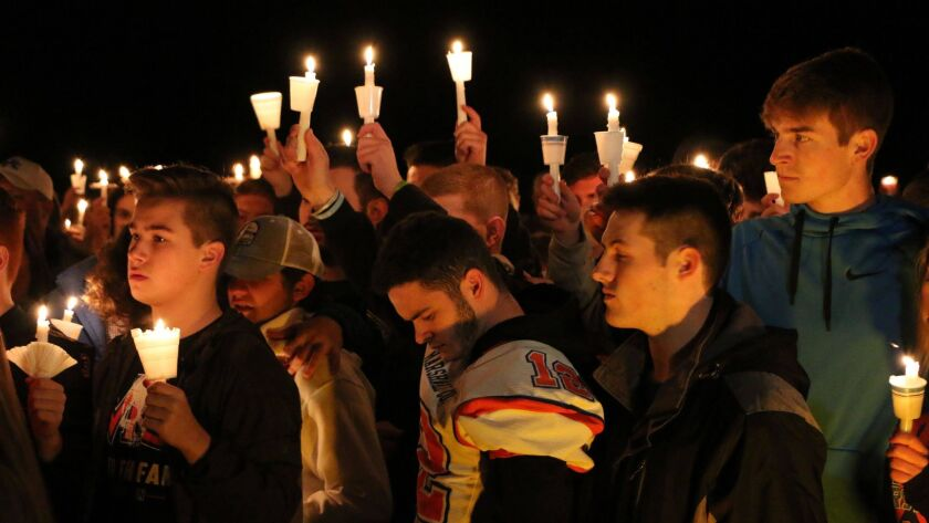 People gather in Benton, Ky., on Thursday night for a vigil honoring the victims of a fatal shooting at Marshall County High School.