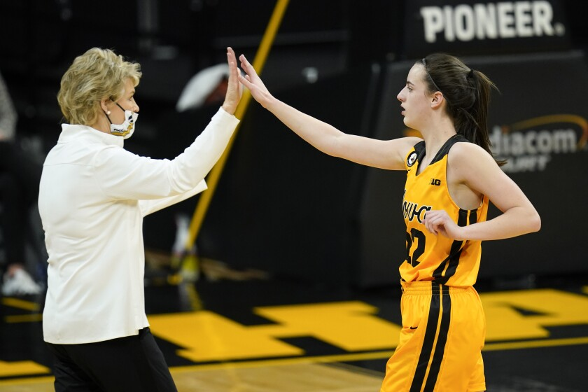 """Iowa guard Caitlin Clark, right, celebrates with coach Lisa Bluder during the first half of the team's NCAA college basketball game against Ohio State, Wednesday, Jan. 13, 2021, in Iowa City, Iowa. Clark is fourth in the nation in scoring, fourth in the nation in assists and ninth in assists per game. She is also second on the team in rebounds and tied for the team lead in blocked shots. """"She's not one-dimensional,"""" Bluder said. (AP Photo/Charlie Neibergall)"""
